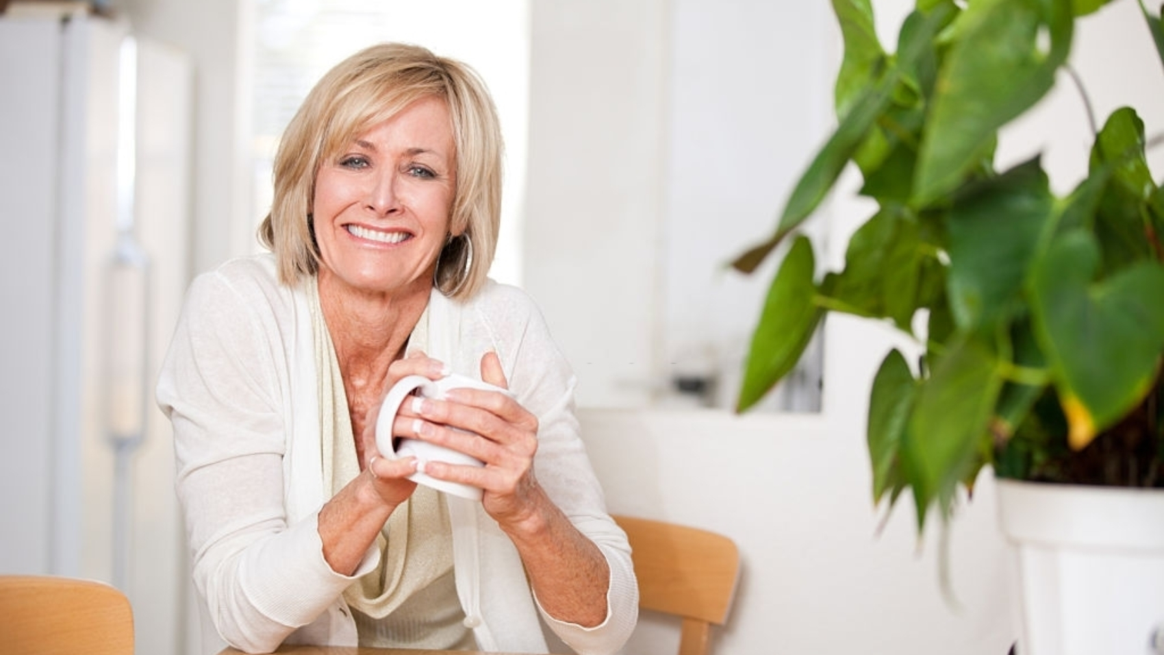 Happy, middle aged woman drinking hot tea in her white kitchen. She is smiling at the camera. Woman is in her 50s and has both hands around the coffee mug. She is very genuine and warm. Green plan in of the right of the image.